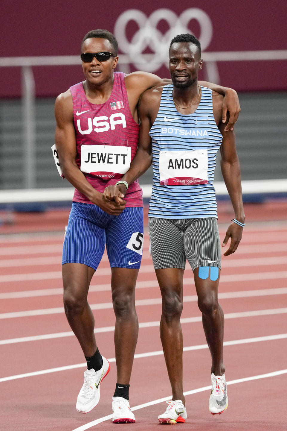 Isaiah Jewett, of the United States, and Nijel Amos, right, of Botswana, walk off after falling in the men's 800-meter semifinal at the 2020 Summer Olympics, Sunday, Aug. 1, 2021, in Tokyo. (AP Photo/Jae C. Hong)