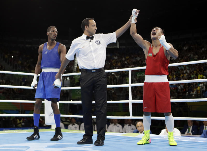 Uzbekistan's Fazliddin Gaibnazarov, right, reacts as he won the gold medal for the men's light welterweight 64-kg boxing against Azerbaijan's Lorenzo Sotomayor Collazo at the 2016 Summer Olympics in Rio de Janeiro, Brazil, Sunday, Aug. 21, 2016. (AP Photo/Frank Franklin II)