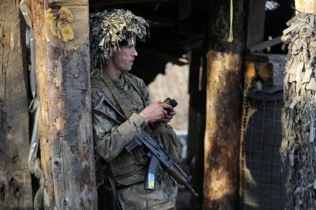 A service member of the Ukrainian armed forces stands guard at fighting positions in Horlivka, near the rebel-controlled city of Donetsk, on Wednesday.