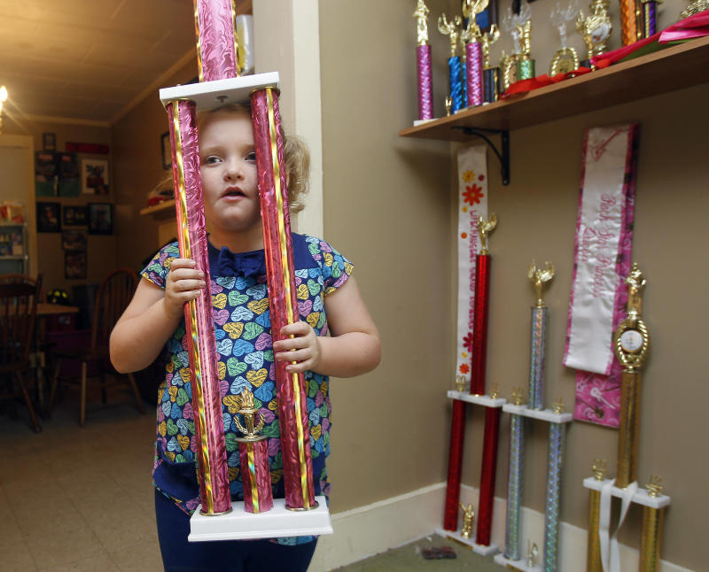 """In this photo taken Monday, Sept. 10, 2012, seven-year-old beauty pageant regular and reality show star Alana """"Honey Boo Boo"""" Thompson shows one of her many trophies in her home in McIntyre, Ga. The reality show """"Here Comes Honey Boo Boo"""" centers around Alana, her mother June Shannon and their family. (AP Photo/John Bazemore)"""
