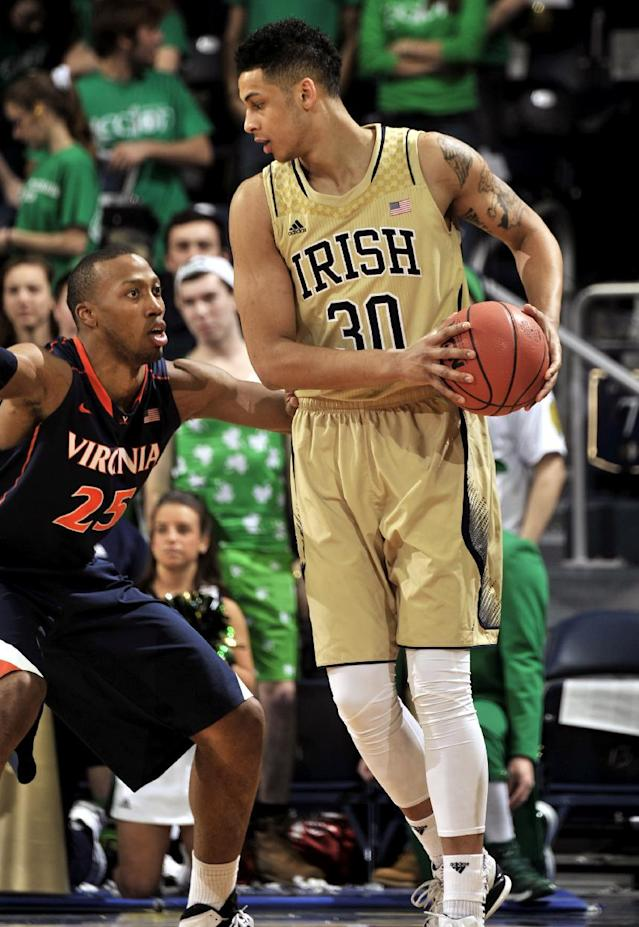 Notre Dame forward Zach Auguste, right, posts up as Virginia forward Akil Mitchell defends during the first half of an NCAA college basketball game, Tuesday, Jan. 28, 2014 in South Bend, Ind. (AP Photo/Joe Raymond)