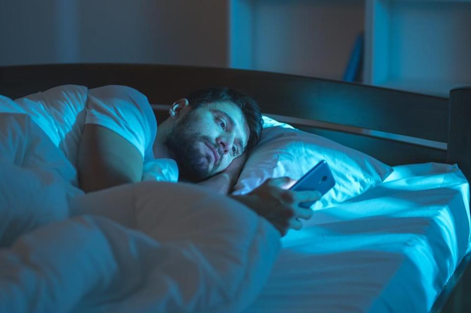 """Putting your phone just out of reach before bed could yield some major health benefits in the long run. One 2011 study published in <em>Neuro Endocrinology Letters</em> noted that the blue light it emits can <a href=""""https://pubmed.ncbi.nlm.nih.gov/21552190/"""" rel=""""nofollow noopener"""" target=""""_blank"""" data-ylk=""""slk:reduce your body's melatonin production"""" class=""""link rapid-noclick-resp"""">reduce your body's melatonin production</a>, making it harder to <a href=""""https://bestlifeonline.com/doctor-approved-full-nights-sleep/?utm_source=yahoo-news&utm_medium=feed&utm_campaign=yahoo-feed"""" rel=""""nofollow noopener"""" target=""""_blank"""" data-ylk=""""slk:get a good night's sleep"""" class=""""link rapid-noclick-resp"""">get a good night's sleep</a>."""