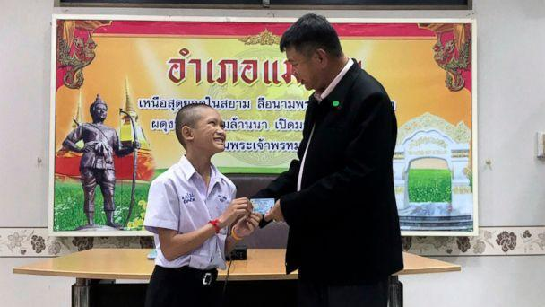 PHOTO: Mongkol Boonpiam, left, receives an identity card denoting Thai citizenship from Somsak Kunkam, Sheriff of Mae Sai during a ceremony in Chiang Rai pro   vince, Thailand, Aug. 8, 2018. (Chiang Rai Public Relations Office via AP)