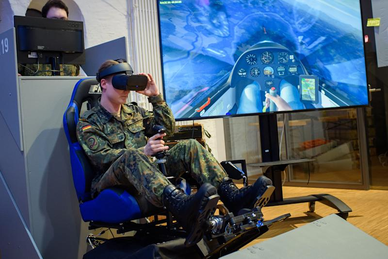 26 November 2019, Berlin: An employee sits in a virtual reality glider simulator during a tour of the Bundeswehr's Cyber Innovation Hub by the Minister of Defence. Photo: Gregor Fischer/dpa (Photo by Gregor Fischer/picture alliance via Getty Images)