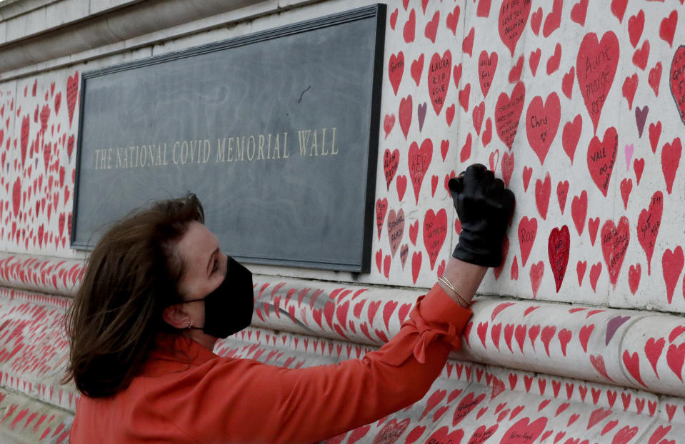 Fran Hall draws the last hearts as families bereaved by Covid-19 mark the completion of the approximately 150,000 hearts being painted onto the National Covid Memorial Wall, on the Thames Embankment opposite the Houses of Parliament in London, Thursday, April 8, 2021. Bereaved families want the wall of painted hearts to remain a site of national commemoration and are asking the Prime Minister to help make the memorial permanent. (AP Photo/Frank Augstein)