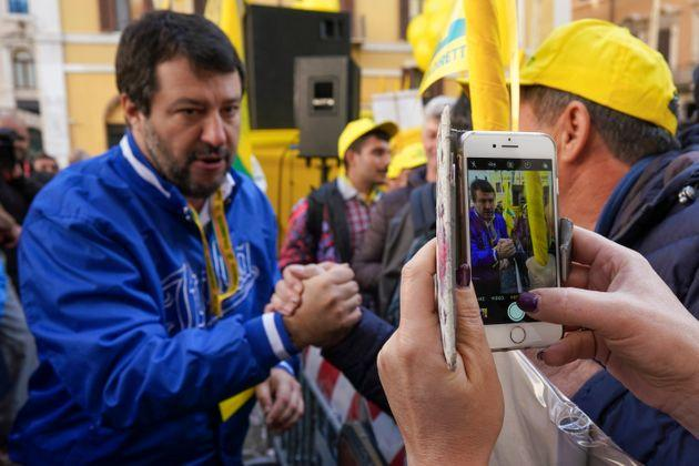 A woman takes pictures of the League leader Matteo Salvini greeting farmers during a protest organized by agricultural lobby Coldiretti against the overpopulation of wild boars and their destruction of farmlands and produce, in Rome, Thursday, Nov. 7, 2019. According to Coldiretti, the population of wild boars has more than doubled in the past ten years, accounting for some 2 million boars in Italy. (AP Photo/Andrew Medichini)