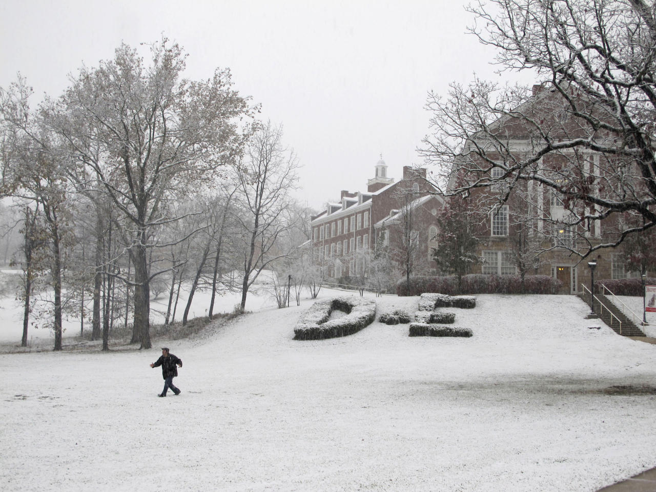 A student walks across the lawn at Davis & Elkins College as the snow started falling hard in Elkins, W. Va., on Monday, Oct. 29, 2012. (AP Photo/Vicki Smith)