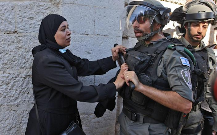A Palestinian woman confronts Israeli security forces outside the Damascus gate in east Jerusalem, on June 15, 2021, ahead of the March of the Flags which celebrates the anniversary of Israel's 1967 occupation of the city's eastern sector. - Israel's new government faced an early test as Jewish ultranationalists prepared to march into annexed east Jerusalem, stoking tensions the UN has warned threaten a fragile Gaza ceasefire. - AFP