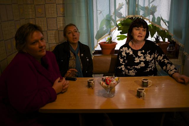 In this picture taken on Wednesday, Nov. 27, 2013, Alexandra Krivchenko, left, Nadezhda Kurovskaya, center, Irina Kharchenko, right, residents of 5a Akatsiy, street drink tea in the village of Vesyoloye outside Sochi, Russia. As the Winter Games are getting closer, many Sochi residents are complaining that their living conditions only got worse and that authorities are deaf to their grievances. (AP Photo/Alexander Zemlianichenko)