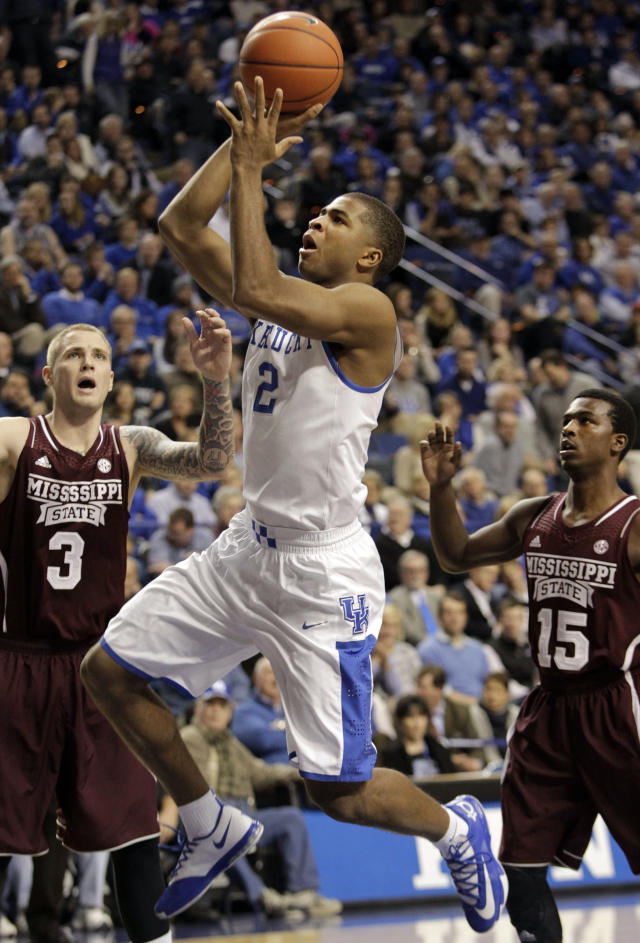 Kentucky's Aaron Harrison (2) shoots near Mississippi State's Colin Borchert (3) and I.J. Ready (15) during the second half of an NCAA college basketball game, Wednesday, Jan. 8, 2014, in Lexington, Ky. Kentucky won 85-63. (AP Photo/James Crisp)