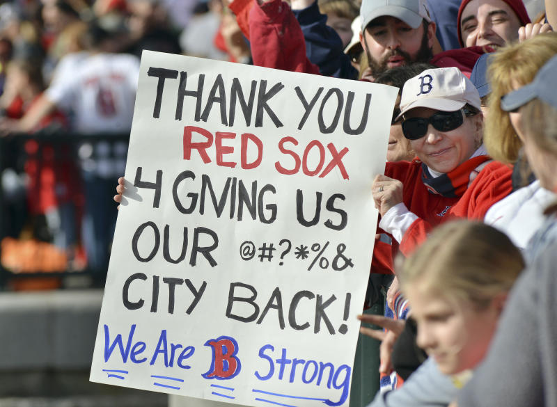 Lisa Jay, of North Reading, Mass., holds a sign while waiting along the bank of the Charles River Saturday, Nov. 2, 2013, in Cambridge, Mass., for Boston Red Sox players to ride past in amphibious duck boats during a rolling victory parade celebrating the team's World Series title. (AP Photo/Josh Reynolds)