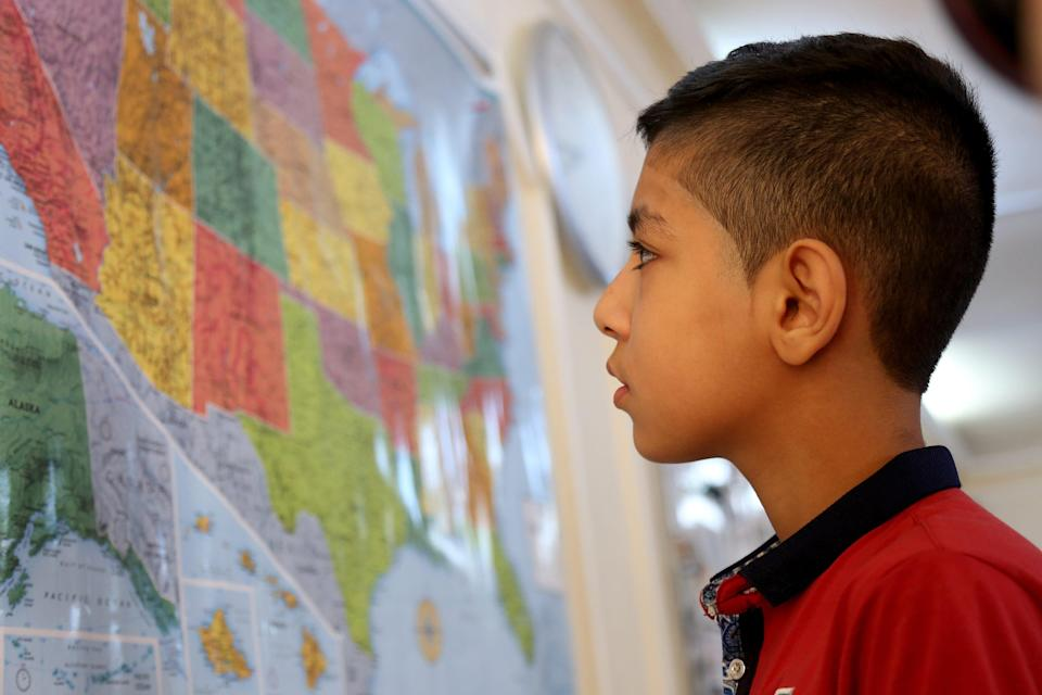 Syrian refugee Hamzeh Jouriyeh, 12, studies a map of the USA in the Amman, Jordan, office of the International Organization for Migration. Jouriyeh, his three siblings and his parents were headed to San Diego as part of a yearlong program in 2016 to resettle 10,000 Syrian refugees in the USA.