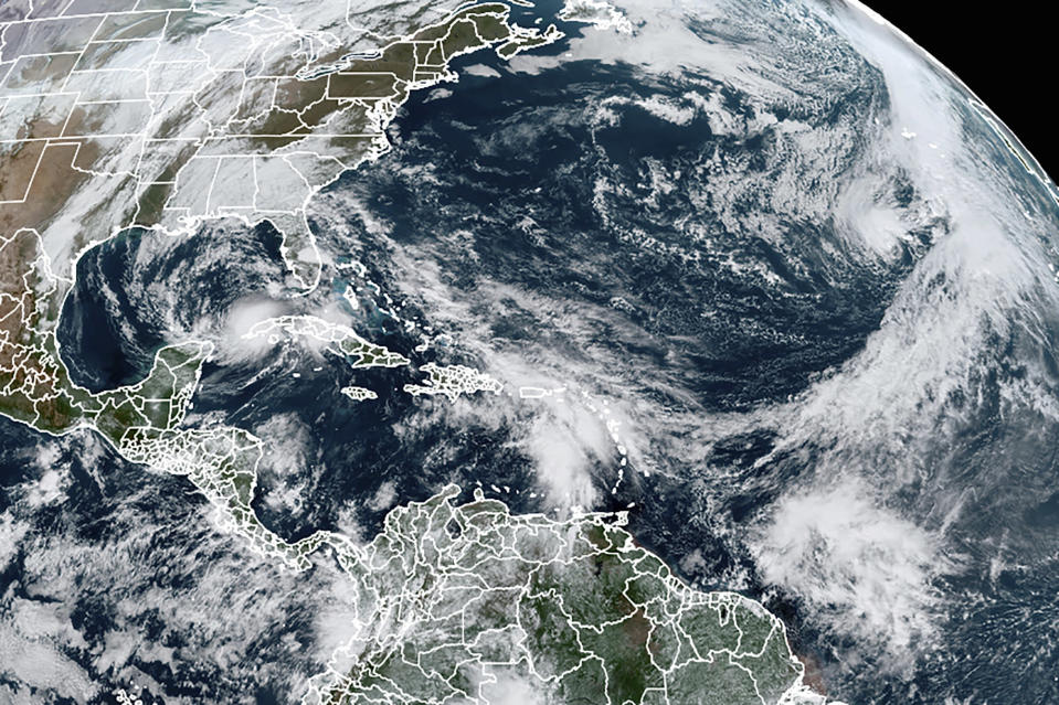 FILE - This Tuesday, Nov. 10, 2020, satellite image made available by NOAA shows Tropical Storm Eta at 10:40 a.m. EST in the Gulf of Mexico, Theta, right, and a tropical wave to the south that became Tropical Storm Iota. An overheating world obliterated weather records in 2020 — an extreme year for hurricanes, wildfires, heat waves, floods, droughts and ice melt — the United Nations' weather agency reported Wednesday, Dec. 2, 2020. (NOAA via AP)