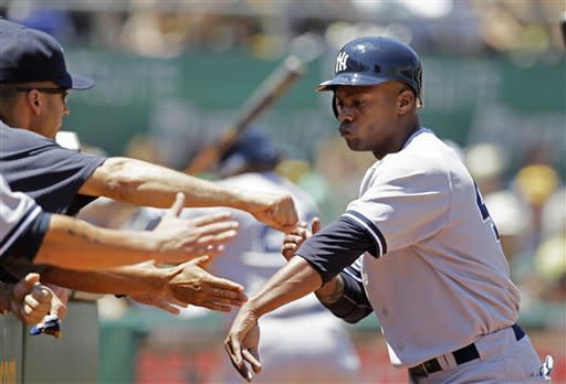 New York Yankees' Dewayne Wise is greeted in the dugout after scoring the Yankees' first run in the third inning of their baseball game against the Oakland Athletics Sunday, July 22, 2012 in Oakland, Calif. (AP Photo/Eric Risberg)