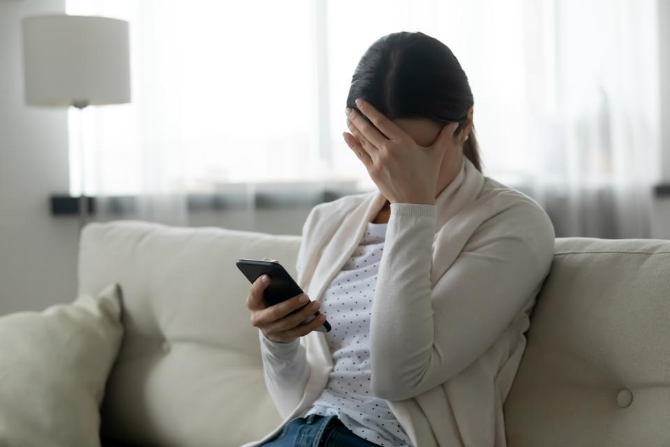 Woman sit on sofa holding smartphone cover face with hand feels scared humiliated suffering from cyberbullying being on-line abused by stalker. Bad news, life troubles, break up with boyfriend concept