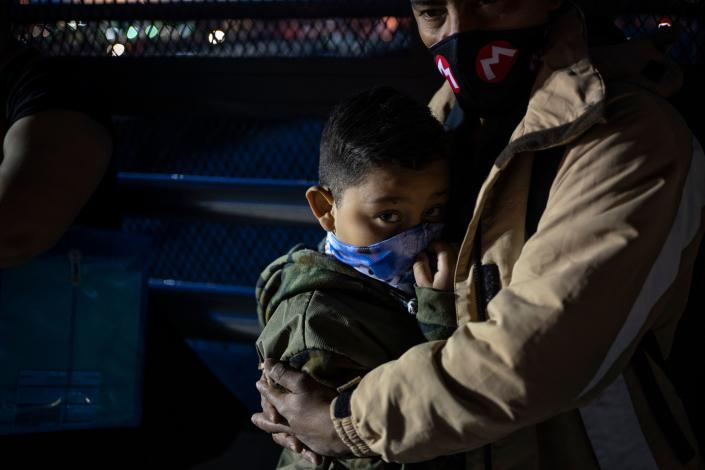 """TOPSHOT - Cesar, 35, an asylum seeker from Nicaragua waits with his eight-year-old son Donovan to enter the US port of entry to change their asylum court dates on April 6, 2020 at the Paso del Norte International Bridge in Ciudad Jua?rez in the state of Chihuahua, Mexico. - As immigration courts have been closed due to the coronavirus, COVID-19, pandemic people seeking asylum in Migrant Protection Protocols program, better known as the """"Remain in Mexico"""" policy, are still expected to show up in the dangerous city centre before dawn to receive new dates despite stay-at-home order on both sides of the border. (Photo by Paul Ratje / Agence France-Presse / AFP) (Photo by PAUL RATJE/Agence France-Presse/AFP via Getty Images)"""