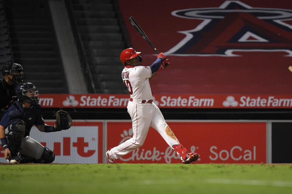 Los Angeles Angels' Justin Upton, right, hits a solo home run as Seattle Mariners catcher Joseph Odom, center, and home plate umpire Edwin Moscoso watch during the sixth inning of a baseball game Wednesday, July 29, 2020, in Anaheim, Calif. (AP Photo/Mark J. Terrill)