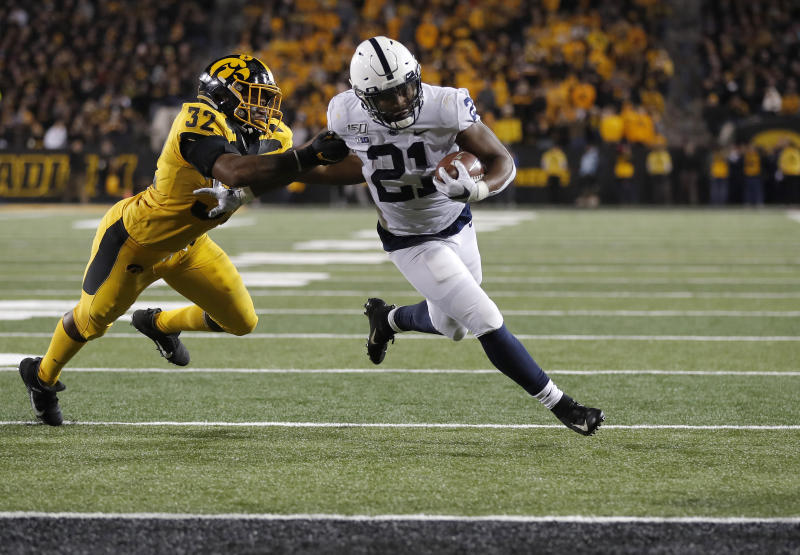 Iowa linebacker Djimon Colbert, left, loses his grasp of Penn State running back Noah Cain as Cain runs in for a touchdown during the second half of an NCAA college football game Saturday, Oct. 12, 2019, in Iowa City, Iowa. (AP Photo/Matthew Putney)
