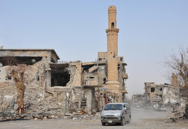 A car drives past a damaged mosque in the eastern Syrian city of Deir Ezzor in this November 5, 2017 file photo