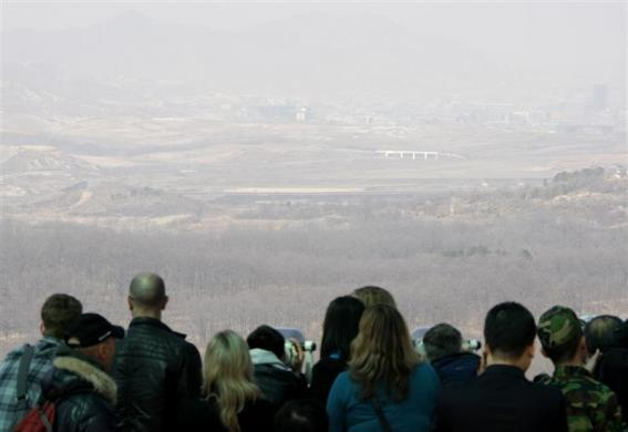 Tourists look towards North Korea on a foggy day from the Dora observation post near the demilitarized zone (DMZ) separating the two Koreas in Paju, north of Seoul, April 2, 2009.