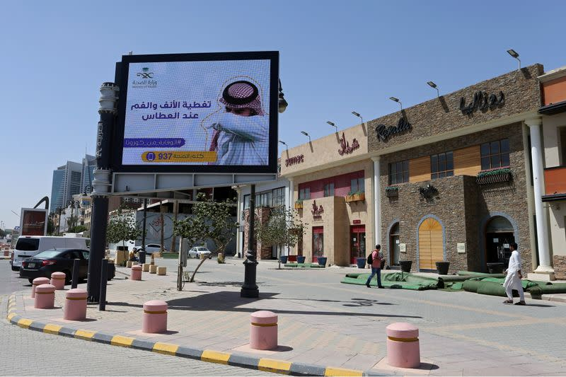 FILE PHOTO: People walk near a banner with an instruction on personnel hygiene, following the outbreak of coronavirus, at a street in Riyadh