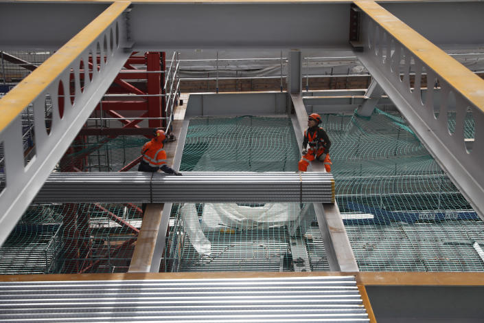 Construction workers put down the steel flooring over the beams at the 8 Bishopsgate development in London, Thursday, April 1, 2021. When the pandemic struck, about 540,000 workers vanished from London's financial hub almost overnight. Developers of 8 Bishopsgate, are confident that when construction ends late next year, workers and firms will return to fill all 50 floors of the gleaming new office space. (AP Photo/Alastair Grant)