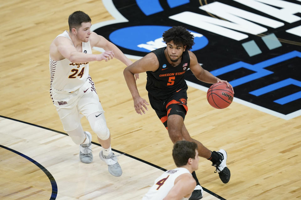 Oregon State guard Ethan Thompson (5) drives past Loyola Chicago guard Tate Hall (24) during the first half of a Sweet 16 game in the NCAA men's college basketball tournament at Bankers Life Fieldhouse, Saturday, March 27, 2021, in Indianapolis. (AP Photo/Darron Cummings)