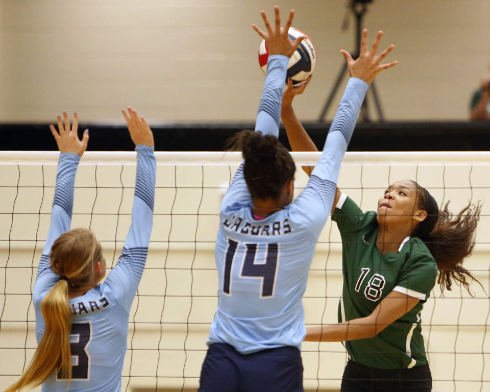 FILE - Reagan's Kyla Waiters, right, spikes the ball past Johnson defenders during a Texas District 26-6A high school volleyball match in San Antonio, Texas, in this Friday, Sept. 22, 2017, file photo. Waiters went on to sign a scholarship at Oregon State. Parents of former Oregon State volleyball players urged the school's trustees to consider president F. King Alexander's handling of abuse allegations in that program while they're discussing his future because of unrelated cases while he was at LSU. In an interview with AP, Kyla's mother, Dorina Waiters, whose daughter transferred to Nevada after one season in Corvallis, said the board did not appear interested in the volleyball case.(Ron Cortes/The San Antonio Express-News via AP, File)