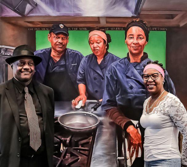 PHOTO: Princeton University residential food service workers Howard Sutphin and Kaniesha Long smile while standing in front of their portrait by Mario Moore. (Hope VanCleaf/Lewis Center for the Arts/Trustees of Princeton)