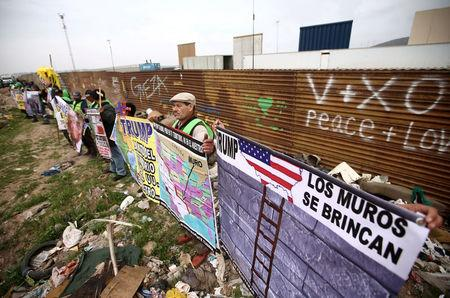 People hold signs during a protest while standing in front of the current border fence and near the prototypes of U.S. President Donald Trump's border wall, in Tijuana, Mexico March 13, 2018. REUTERS/Edgard Garrido