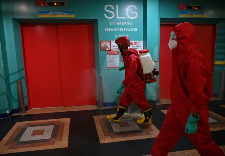 Indonesian fire fighters spray disinfectant at a business center on the last day of the lockdown amid the COVID-19 coronavirus pandemic in Jakarta