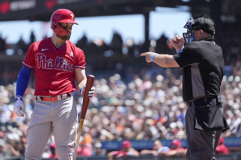 Philadelphia Phillies' Bryce Harper, left, looks at home plate umpire Greg Gibson, right, as he is called out on strikes during the sixth inning against the San Francisco Giants during a baseball game Sunday, June 20, 2021, in San Francisco. (AP Photo/Tony Avelar)