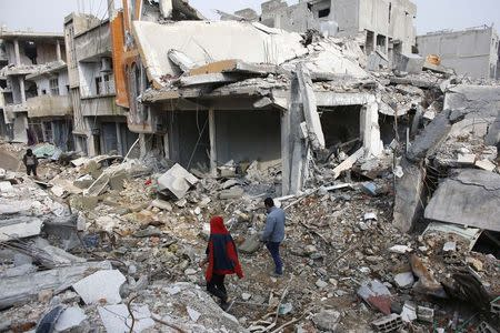 People walk on the debris of damaged buildings in the northern Syrian town of Kobani