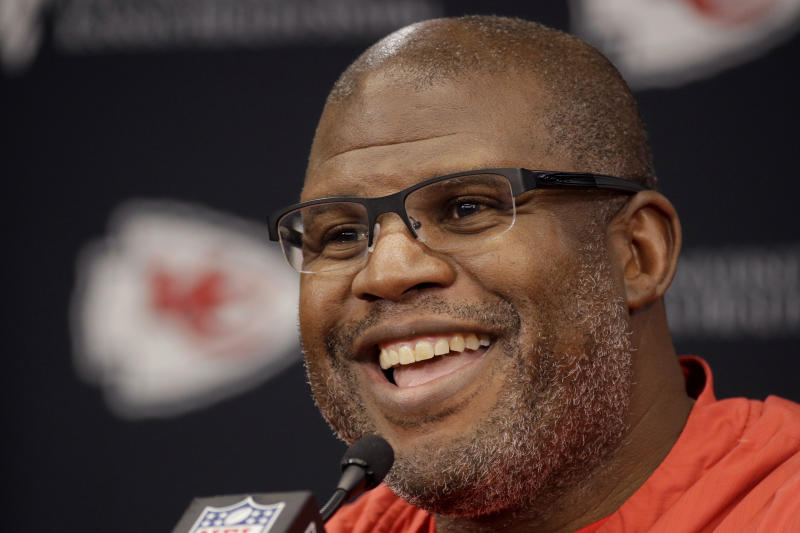 Eric Bieniemy smiles while answering questions during a Super Bowl media session.