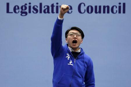 FILE PHOTO: Edward Leung, a candidate from the Hong Kong Indigenous, chants slogans on the podium before the final poll result is announced in Hong Kong