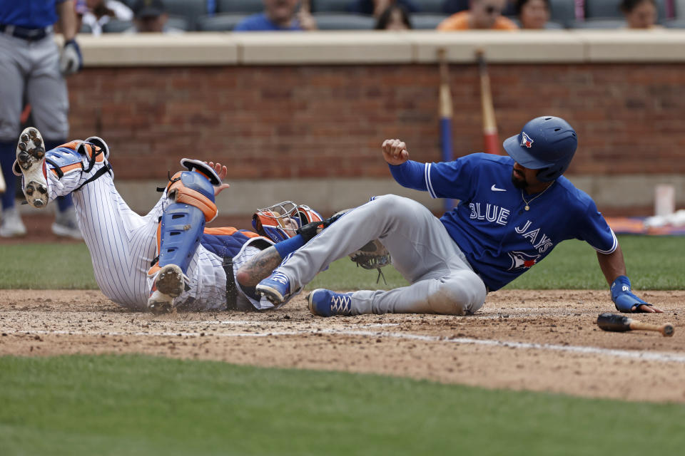 Toronto Blue Jays' Marcus Semien scores a run in front of New York Mets catcher Tomas Nido in the sixth inning during a baseball game Sunday, July 25, 2021, in New York. (AP Photo/Adam Hunger)