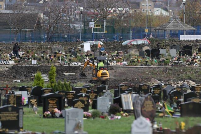 Workers use machinery to dig graves next to the Muslim burial ground at the Scholemoor Cemetery and Crematorium, in Bradford, West Yorkshire (Danny Lawson/PA)