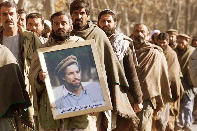 An Afghan man holds a portrait of the late Ahmad Shah Masood, main leader of the Northern Alliance assasinated by suspected al-Qaeda terrorists, as supporters walk to a mosque in Kabul on December 5, 2001 (AFP Photo/Jimin Lai)