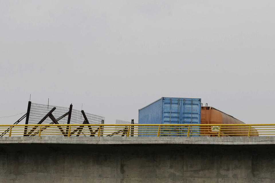 A fuel tanker, cargo trailers and makeshift fencing are used as barricades by Venezuelan authorities attempting to block humanitarian aid entering from Colombia on the Tienditas International Bridge that links the two countries as seen from the outskirts of Cucuta, Colombia, Wednesday, Feb. 6, 2019. Immigration authorities say the Venezuelan National Guard built the roadblock a day earlier. (AP Photo/Fernando Vergara)