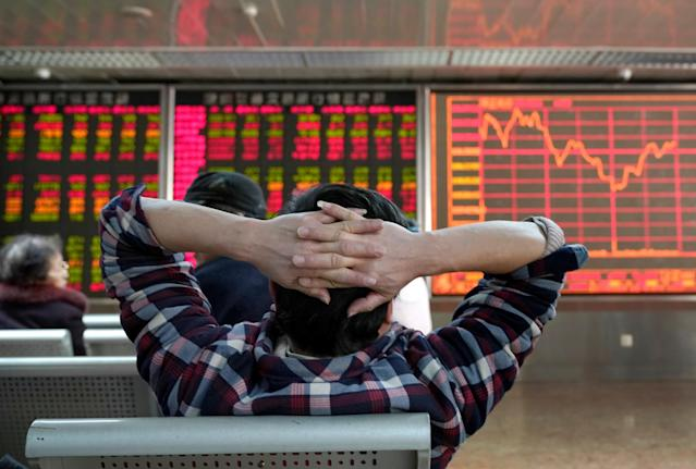 An investor looks at a stock quotation board at a brokerage office in Beijing, China. Photo: Jason Lee/Reuters