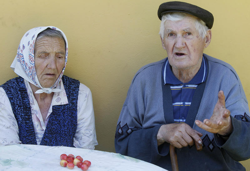 Stanislaw Banach, right, and his wife Genowefa, talk to The Associated Press in their farmyard near Chlaniów, Poland, on Wednesday, June 19, 2013, about the attack on the village by the Nazi SS-led Ukrainian Self Defense Legion in 1944, in which Banach's father and 43 other villagers were killed. An investigation by the AP revealed that a commander in the legion, Michael Karkoc, 94, is living in the United States. In his Ukrainian-language memoirs Karkoc said he was in Chlaniów at the time of the attack. No records uncovered by the AP link him directly to atrocities. (AP Photo/Czarek Sokolowski)