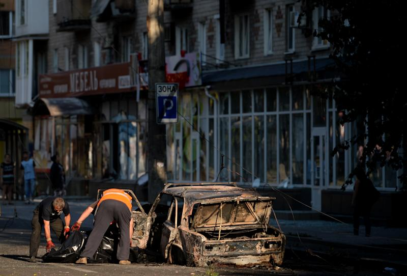 Officials remove a corpse from a burned car in downtown Donetsk, eastern Ukraine on August 27, 2014 (AFP Photo/Francisco Leong)