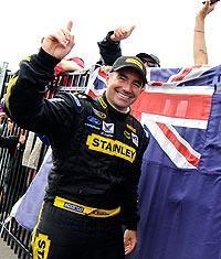 Australian-born Marcos Ambrose celebrates his first career Cup victory next to his native flag