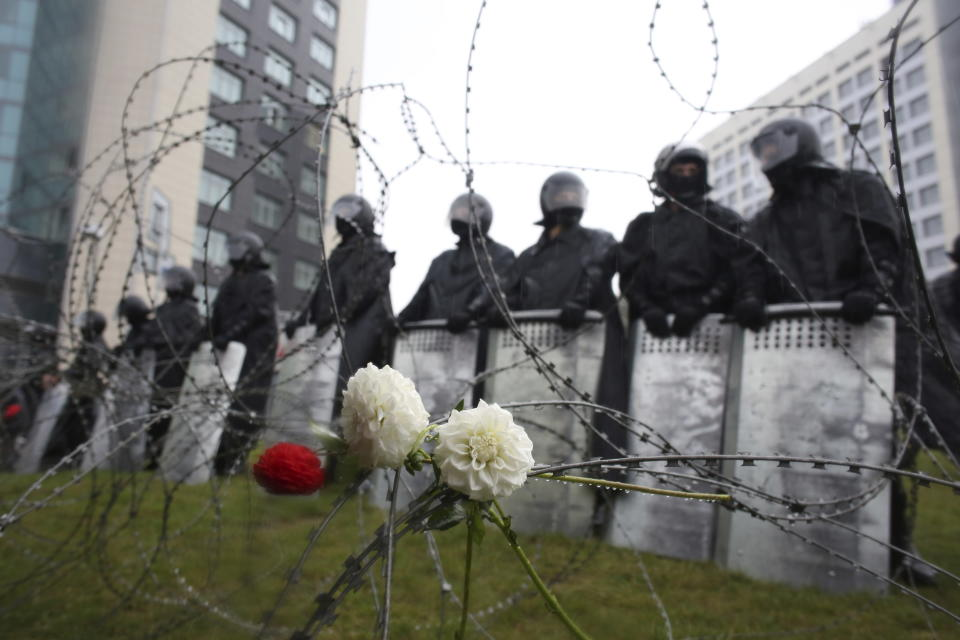 Flowers lie on a barbed wire fence in front of a police line toward the Independence Palace, residence of the President Alexander Lukashenko, during Belarusian opposition supporters rally in Minsk, Belarus, Sunday, Sept. 6, 2020. Sunday's demonstration marked the beginning of the fifth week of daily protests calling for Belarusian President Alexander Lukashenko's resignation in the wake of allegedly manipulated elections. (AP Photo/TUT.by)