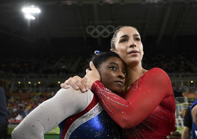 2016 Rio Olympics - Artistic Gymnastics - Final - Women's Individual All-Around Final - Rio Olympic Arena - Rio de Janeiro, Brazil - 11/08/2016. Silver medal winner Alexandra Raisman (USA) of the U.S. hugs compatriot and gold medal winner Simone Biles (USA) . REUTERS/Dylan Martinez FOR EDITORIAL USE ONLY. NOT FOR SALE FOR MARKETING OR ADVERTISING CAMPAIGNS.