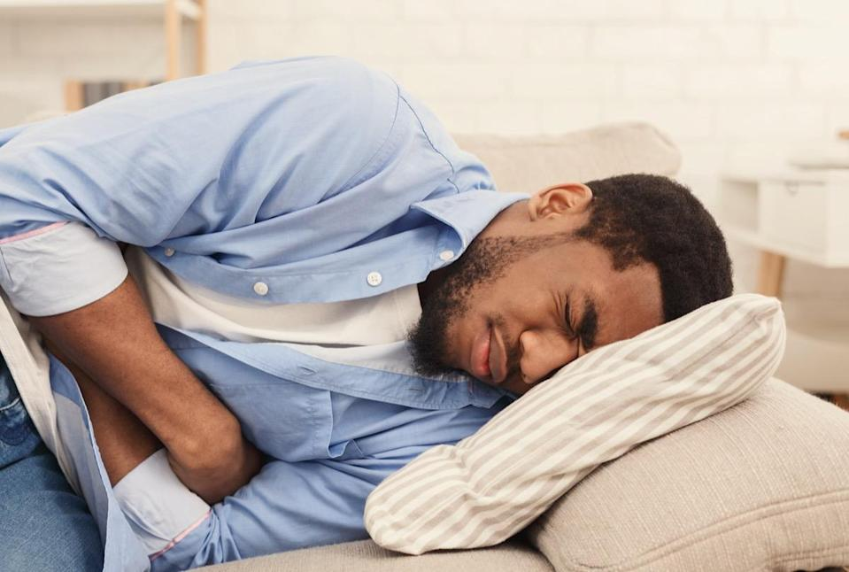 African-american man suffering from stomach ache, lying on sofa at home