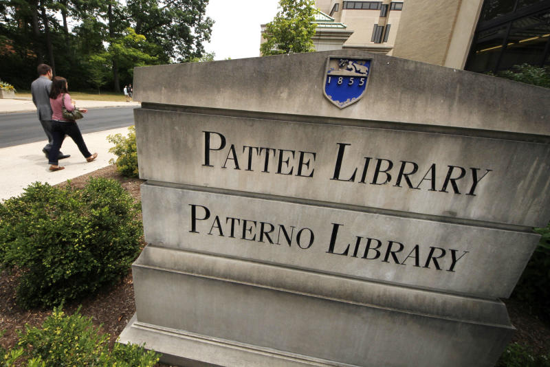 People pass the sign outside the Pattee and Paterno Library on the main campus of Penn State University in State College, Pa., Friday, July 13, 2012. (AP Photo/Gene J. Puskar)