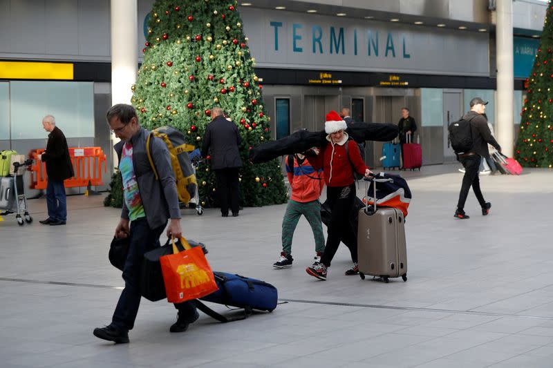 Passengers walk with suitcases in Gatwick Airport, in Crawley