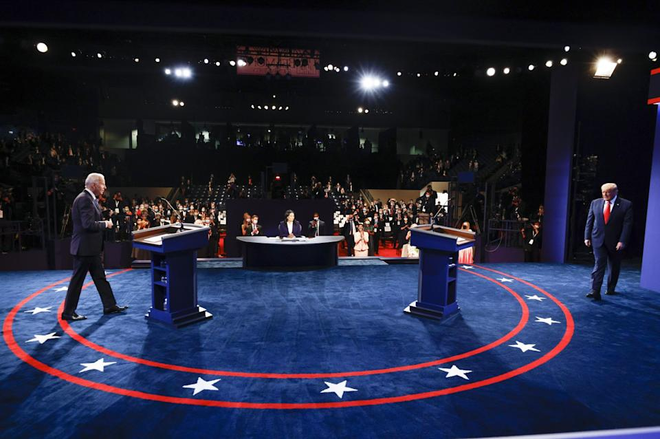 President Trump and Joe Biden walk onto a blue carpeted debate stage