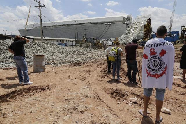 A metal structure that buckled is seen atop a part of the Itaquerao Stadium in Sao Paulo, Brazil, Wednesday, Nov. 27, 2013. Part of the Itaquerao stadium that will host the 2014 World Cup opener in Brazil collapsed on Wednesday, causing significant damage and killing three people, authorities said. (AP Photo/Nelson Antoine)